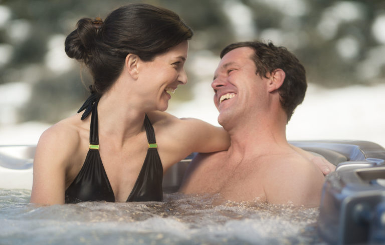 Woman and man soaking in a Sundance Spas hot tub.