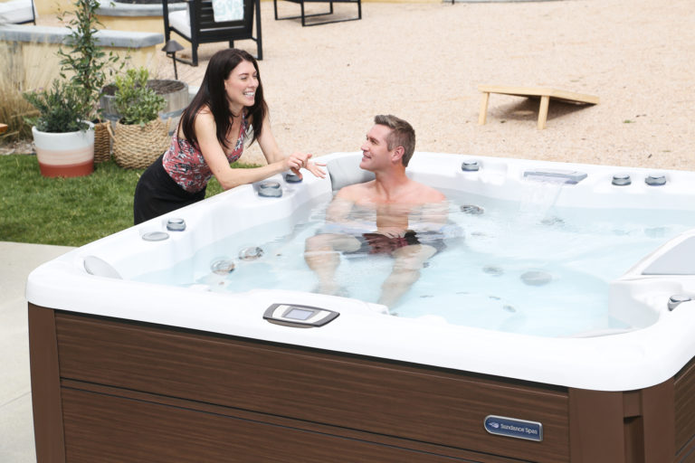 Man talking to woman while soaking in the hot tub.