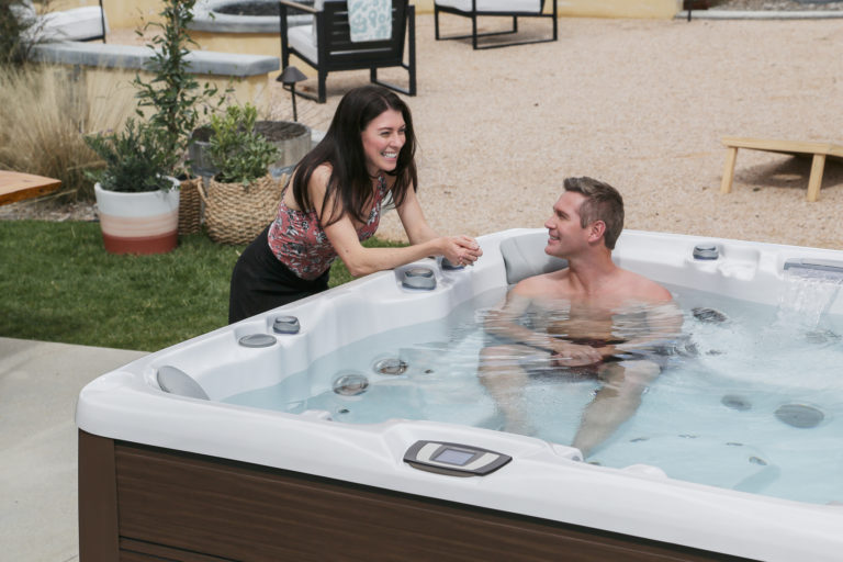 Man soaking in a hot tub and talking to his wife.